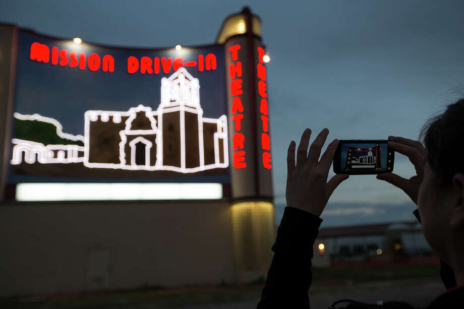 Dina Zavala takes a photo of her handiwork during the official lighting of the recently completed Mission Drive-In Mural at the Mission Drive-In Theatre on Feb. 12, 2013. Zavala, an employee of SRO Associates, worked on the design, painting, neon and marquee of the mural. Photo: Michael Miller, For The Express-News / For the Express-News