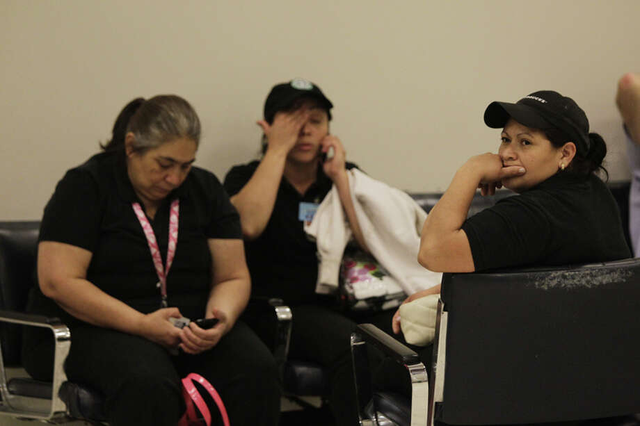 Starbuck employees Juanita Martinez, left, Erika Gozman, center, and Daisy Ochoa , right, wait on baggage level to be allowed to go to the employee parking level after a shooting in Terminal B at Bush Intercontinental Airport, Thursday, May 2, 2013.