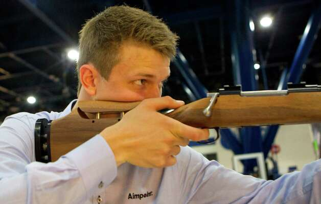 Alexander Nordin calibrates a hunting simulator in the Aimpoint booth as exhibitors began setting up in preparation for the National Rifle Association's 142 Annual Meetings and Exhibits at the George R. Brown Convention Center Thursday, May 2, 2013, in Houston. 