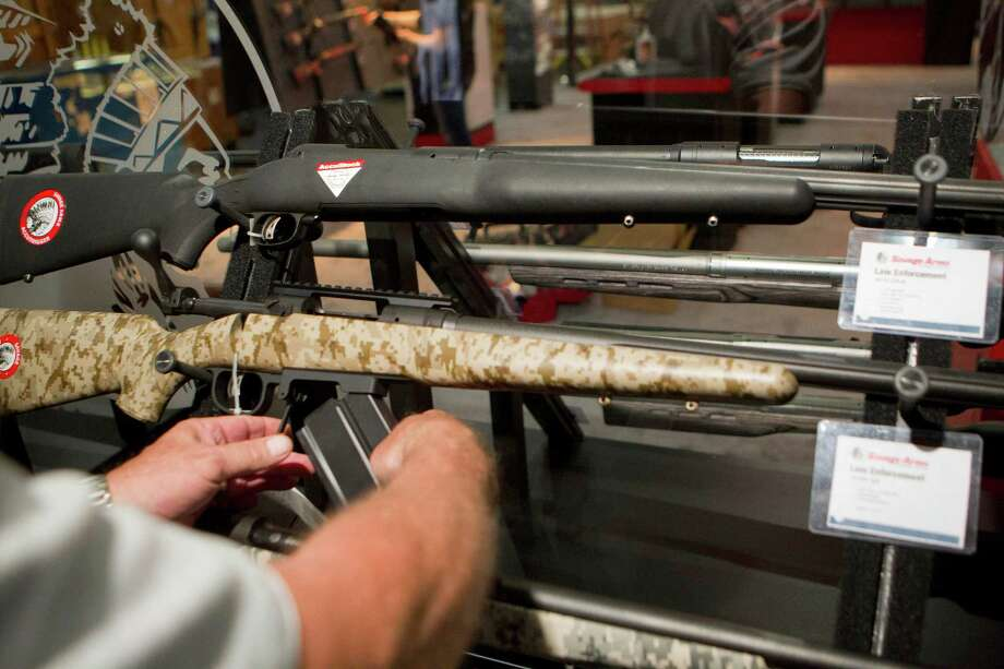 Jim Bentley gets a closer look at a gun in the Savage Arms booth as exhibitors began setting up in preparation for the National Rifle Association's 142 Annual Meetings and Exhibits at the George R. Brown Convention Center Thursday, May 2, 2013, in Houston. 