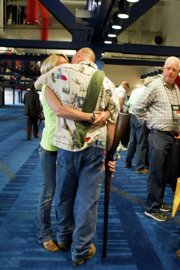 Barry Bailey, of DeRidder La., gives his wife Judy a kiss, before having their 1873 Winchester shotgun appraised at the NRA's Antiques Guns and Gold Showcase during the National Rifle Association's 142 Annual Meetings and Exhibits at the George R. Brown Convention Center Thursday, May 2, 2013, in Houston.  NRA's Antiques Guns and Gold Showcase is a television show that runs on the Sportsman Channel. The 2013 NRA Annual Meetings and Exhibits runs from Friday, May 3, through Sunday, May 5.  More than 70,000 are expected to attend the event with more than 500 exhibitors represented. The convention will features training and education demos, the Antiques Guns and Gold Showcase, book signings, speakers including Glenn Beck, Ted Nugent and Sarah Palin as well as NRA Youth Day on Sunday Photo: Johnny Hanson, Houston Chronicle / © 2013  Houston Chronicle
