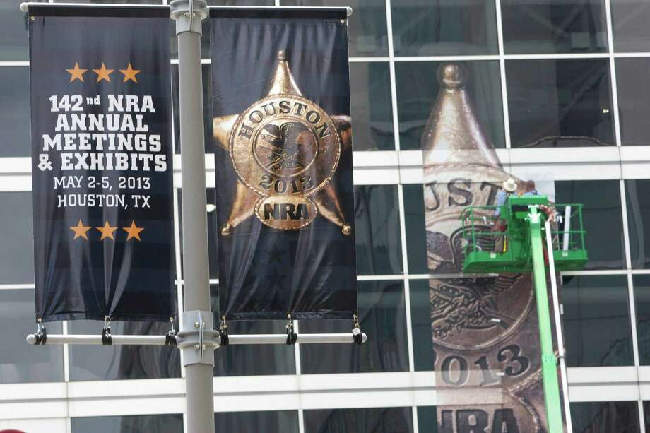 The National Rifle Association's 142 Annual Meetings and Exhibits logo is placed on the George R. Brown Convention Center Wednesday, May 1, 2013, in Houston.  The 2013 NRA Annual Meetings and Exhibits runs from Friday, May 3, through Sunday, May 5.  More than 70,000 are expected to attend the event with more than 500 exhibitors represented. The convention will features training and education demos, the Antiques Guns and Gold Showcase, book signings, speakers including Glenn Beck, Ted Nugent and Sarah Palin as well as NRA Youth Day on Sunday Photo: Johnny Hanson, Houston Chronicle / © 2013  Houston Chronicle