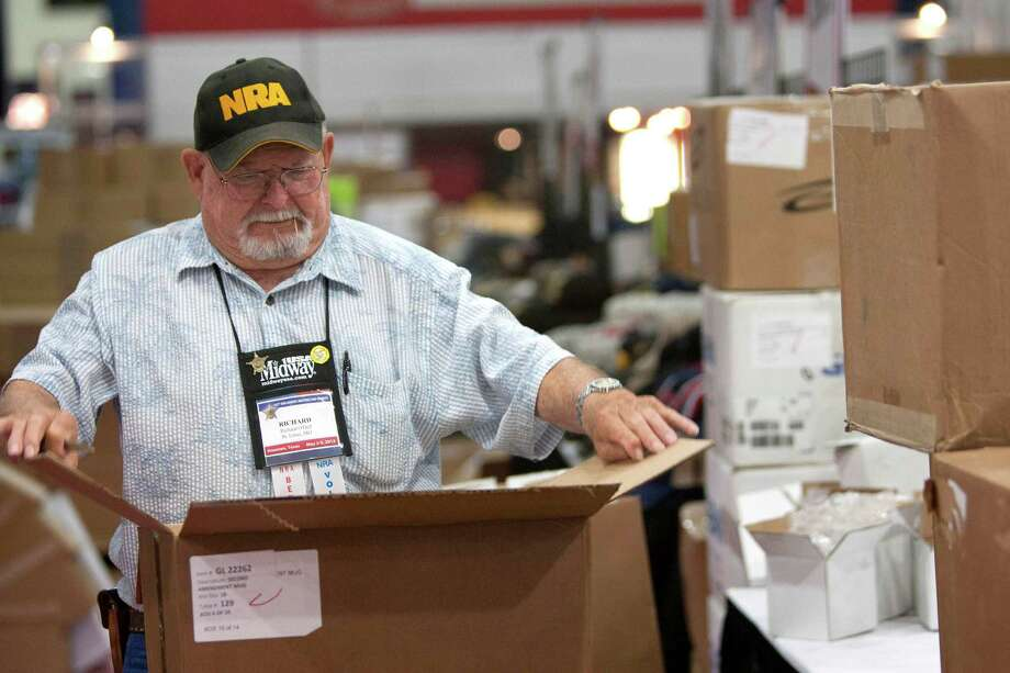 Richard O'Dell, unpacks goods to be sold at the NRA Store as exhibitors began setting up in preparation for the National Rifle Association's 142 Annual Meetings and Exhibits at the George R. Brown Convention Center Wednesday, May 1, 2013, in Houston.  The 2013 NRA Annual Meetings and Exhibits runs from Friday, May 3, through Sunday, May 5.  More than 70,000 are expected to attend the event with more than 500 exhibitors represented. The convention will features training and education demos, the Antiques Guns and Gold Showcase, book signings, speakers including Glenn Beck, Ted Nugent and Sarah Palin as well as NRA Youth Day on Sunday Photo: Johnny Hanson, Houston Chronicle / © 2013  Houston Chronicle