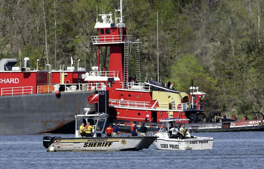 New York State Police and an Ulster County Sheriff boats search the Hudson River on Friday, May 3, 2013, for small plane that crashed on Thursday, as a tug boat passes  in Germantown, N.Y. Authorities say there were no survivors found by the time they suspended their search Thursday night. (AP Photo/Mike Groll) Photo: Mike Groll