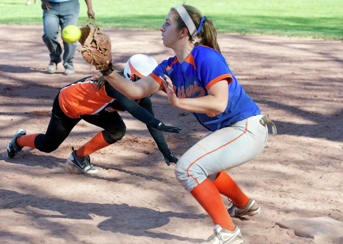 Danbury's Noelle Daley reaches for the ball at first base as Stamford's Haley Lamotta dives safely back to the bag during Friday's softball game at Stamford High School on May 3, 2013.