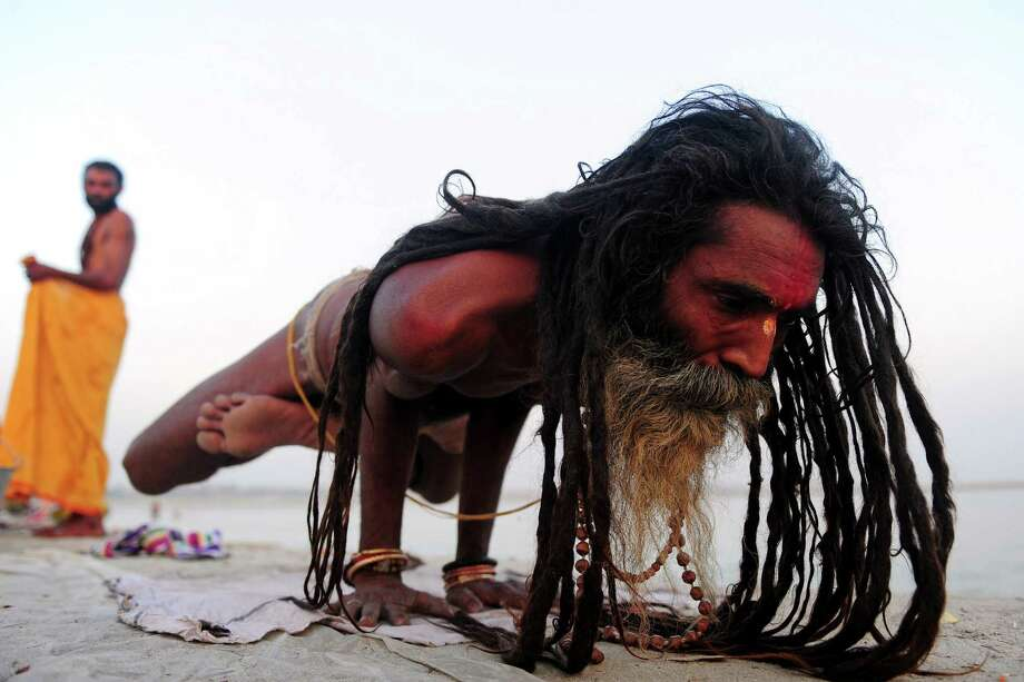 An Indian Hindu Sadhu (holy man) performs yoga on the banks of the Sangam in Allahabad on Tuesday. Yoga, which means union in Sanskrit, is a family of ancient spiritual practices and also a school of spiritual thought from the Asian subcontinent. Photo: Sanjay Kanojia / AFP / Getty Images