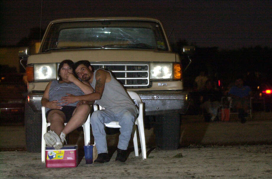 "Jeannie Lozano, 28, and husband Rudy Lozano, 36, who have been patrons of the Mission Drive-In in San Antonio for ten years, watch ""The Mummy Returns"" on May 8, 2001. About 150 carloads of people turned out for the soft opening. Photo: Maria J. Avila, EXPRESS-NEWS FILE PHOTO / SAN ANTONIO EXPRESS-NEWS"