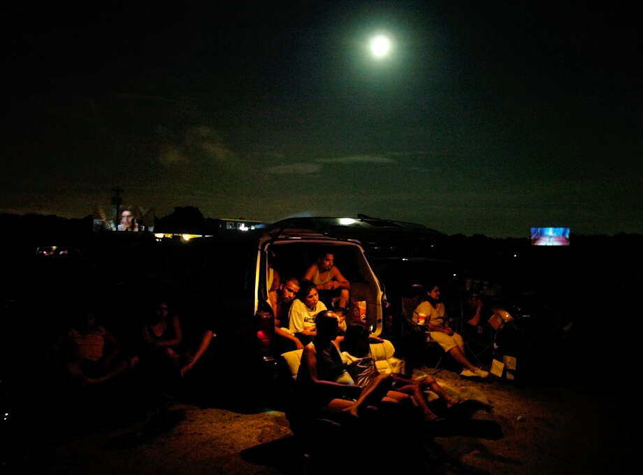 "A family gathers to watch ""Spiderman 2"" at the Mission Drive-In Theatre on, June 30, 2004.  Photo: BAHRAM MARK SOBHANI, SAN ANTONIO EXPRESS-NEWS / SAN ANTONIO EXPRESS-NEWS"