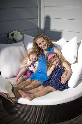 Lisa Sugar poses for a portrait on her chaise lounge with her daughters at her home in San Francisco, CA Friday April 12th, 2013.