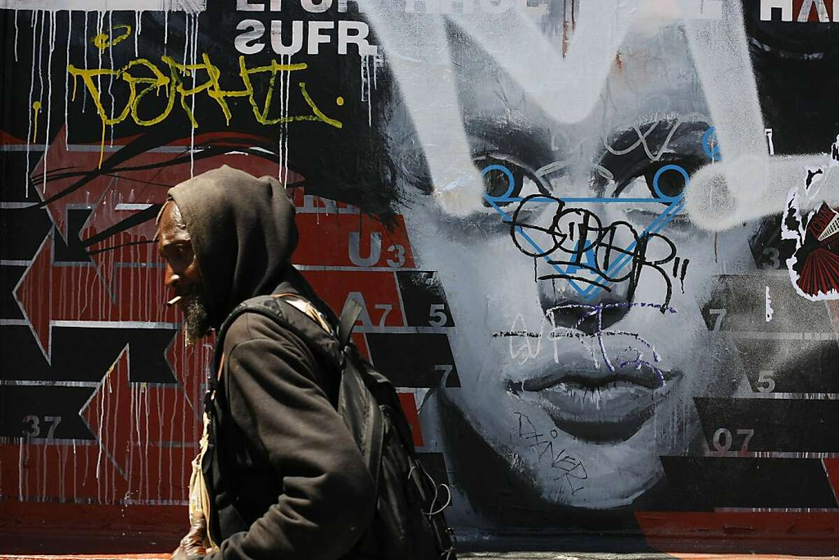 A man passes tagged street art on Polk St. on Friday, May 3 in San Francisco, Calif. Merchants near Sutter and Larkin say that graffiti and tagging has increased ever since a graffiti supply store opened up in the area.