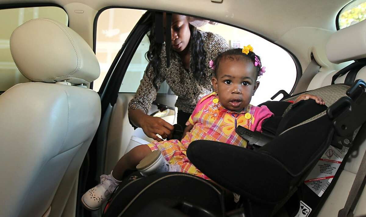 Shanell White removes her daughter Imani Rose, 1 from her new-used car Thursday, April 18, 2013 in Elk Grove, Calif. White is one of thousands of Californian's who have been victimized by second market vehicle lenders. White took out a loan secured by her 1999 car when she needed money to make her rent. The loan came with 79.9% interest. After three years of making payments she was told she still owed the original balance. She now drives a car purchased by her child's father.