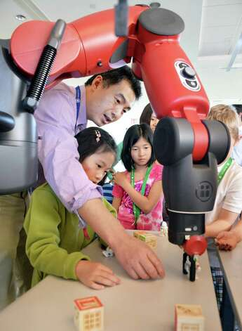 "GE researcher Li Zhang demonstrates ""Baxter"", a robot they?re considering using as part of a surgical automation project with the VA, to his daughter Stella Zhang, 6, left, of Clifton Park and Lina Kim,9, left of Niskayuna during GE Global Research's annual ?Bring Your Child to Work Day? in Niskayuna,NY May 3, 2013.   (John Carl D'Annibale / Times Union) Photo: John Carl D'Annibale / 10022259A"