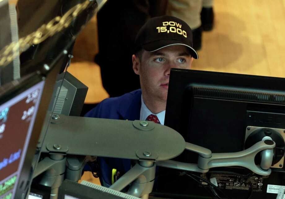 "Specialist Frank Masiello wears a ""Dow 15,000"" hat as he works at his post on the floor of the New York Stock Exchange Friday, May 3, 2013. A big gain in the job market is lifting the stock market to a record high. The Dow Jones industrial average crossed 15,000 for the first time, and the Standard and Poor's 500 index, a broader market measure, rose above 1,600.(AP Photo/Richard Drew) Photo: Richard Drew"