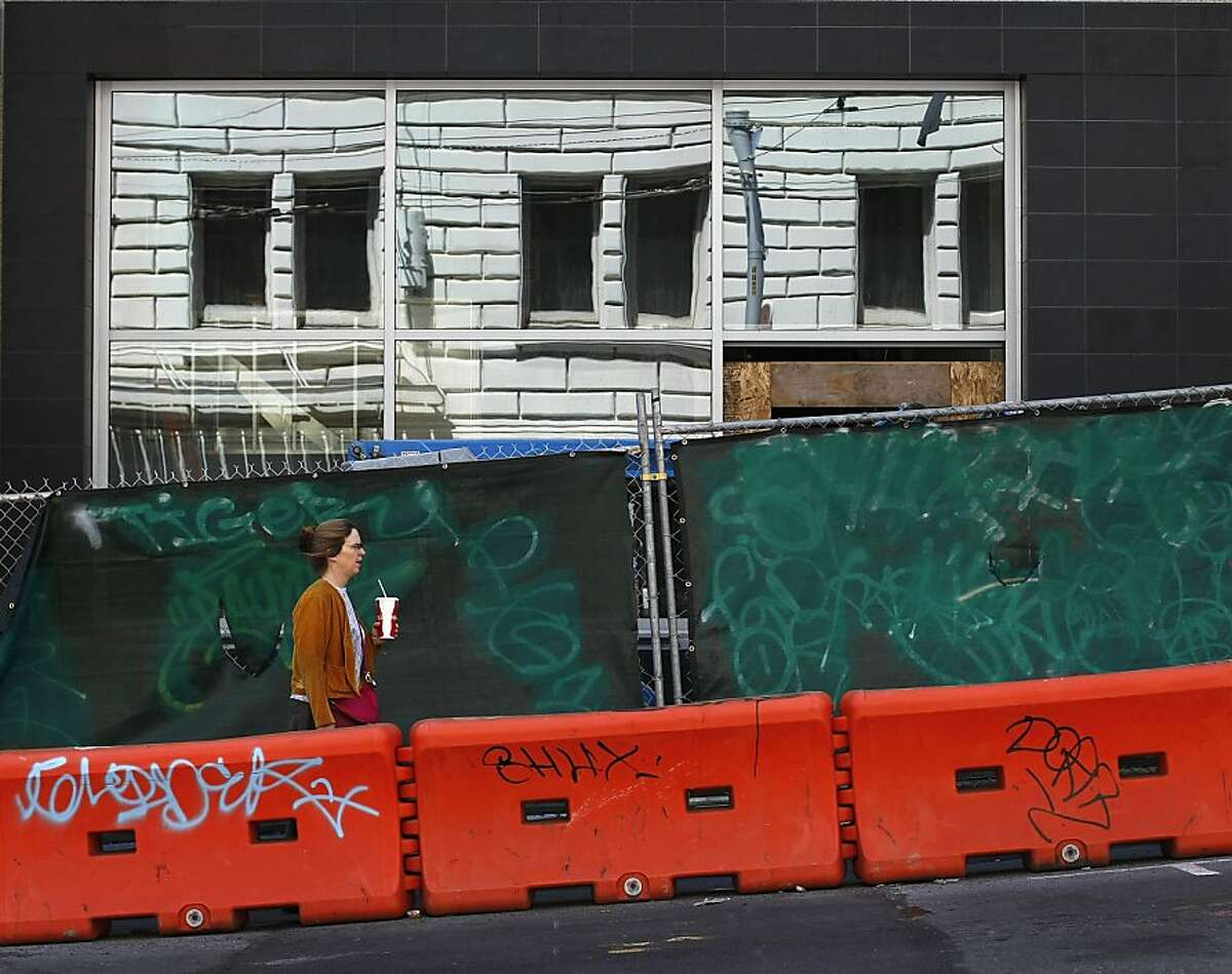 A woman passes a tagged construction area as she makes her way down Sutter St. in San Francisco, Calif. on Friday, May 3. Merchants near Sutter and Larkin say that graffiti and tagging has increased ever since a graffiti supply store opened up in the area.