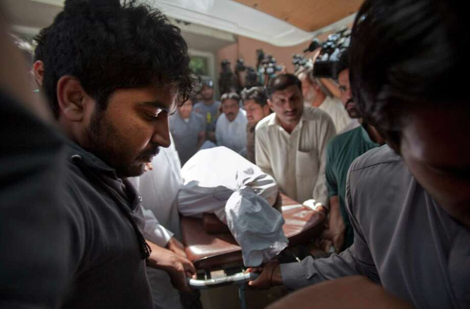 Relatives of prosecutor Chaudhry Zulfikar Ali, assassinated hours earlier by gunmen, leave an Islamabad morgue with his body on Friday. Photo: Anjum Naveed, STF / AP