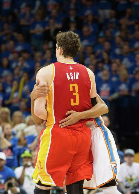 """Rockets center Omer Asik, left, wasn't feeling the love in Game 5. Rather than a hug, Thunder guard Thabo Sefolosha was implementing """"Hack-a-Turk."""" Photo: Smiley N. Pool, Staff / © 2013  Houston Chronicle"""