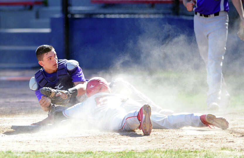 Westhill catcher Joey DePreta, left, looks to the umpire as Cam Fennell of Greenwich is covered in a