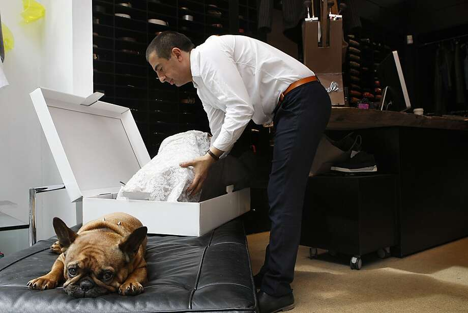 San Francisco designer Gus Harput packs up a wedding dress he made for Katy Bennett, his first one, after she walked into his shop after spotting Lulu the bulldog in the window. Photo: Liz Hafalia, The Chronicle