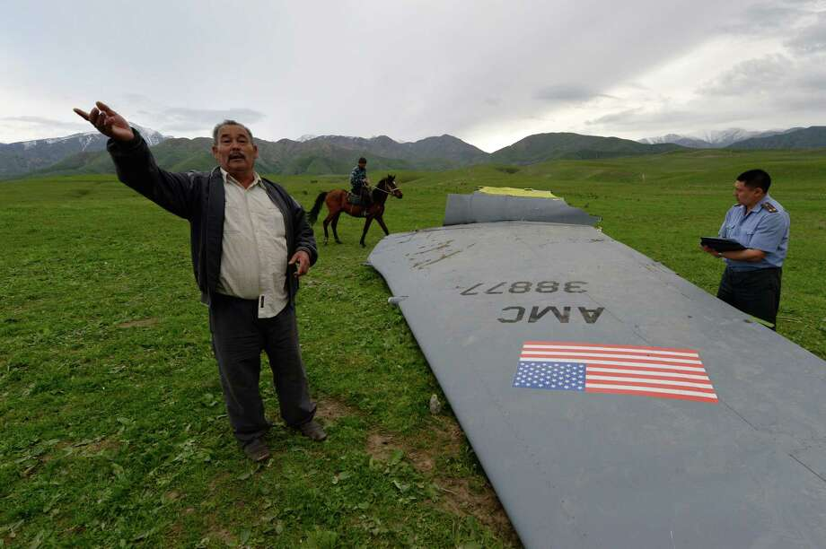 A Kyrgyz policeman investigates a U.S. Air Force KC-135 tanker aircraft wreckage as a local citizen speaks to The Associated Press photographer on a field near the village of Chaldovar, about 100 miles (160 kms) west of the Kyrgyz capital Bishkek, Friday, May 3, 2013. The emergencies ministry in Kyrgyzstan says a US military plane has crashed in the country. Kyrgyzstan hosts a US base that is used for troops transiting into and out of Afghanistan and for C-135 tanker planes that refuel warplanes in flight. (AP Photo/Vladimir Voronin) Photo: Vladimir Voronin, STR / AP