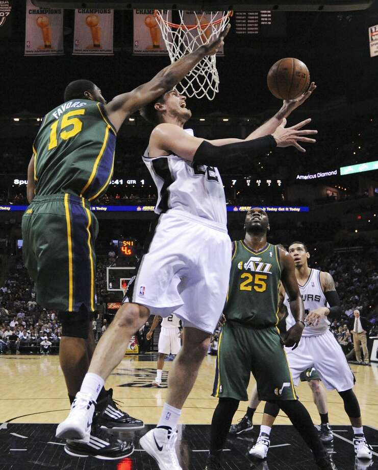 San Antonio Spurs' Tiago Splitter shoots around Utah Jazz's Derrick Favors during first half action Friday March 22, 2013 at the AT&T Center. The Spurs won 104-97 in overtime.
