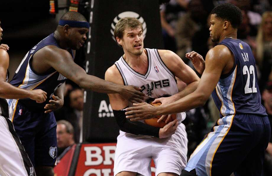 After rebounding the ball, San Antonio Spurs' Tiago Splitter guards the ball from Memphis Grizzlies' Zach Randolph, left, and Rudy Gay during the second half at the AT&T Center, Wednesday, Jan. 16, 2013. The Spurs won 103-82. Photo: Jerry Lara, San Antonio Express-News / © 2013 San Antonio Express-News