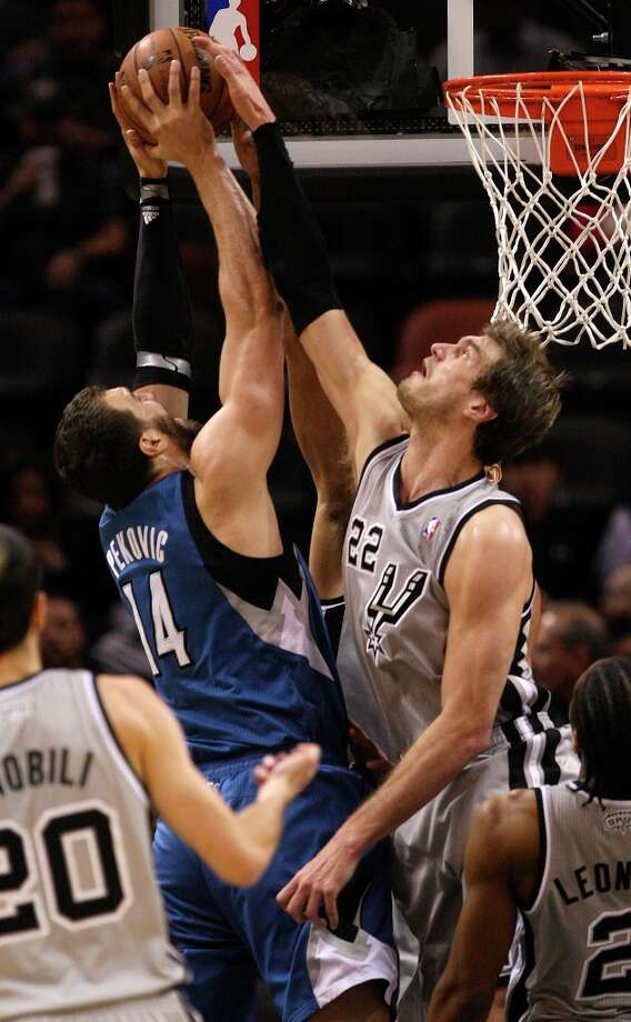 San Antonio Spurs' Tiago Splitter attempts to block a shot by Minnesota Timberwolves' Nikola Pekovic in the first half at the AT&T Center, Sunday, Jan. 13, 2013. Photo: Jerry Lara, San Antonio Express-News / © 2013 San Antonio Express-News