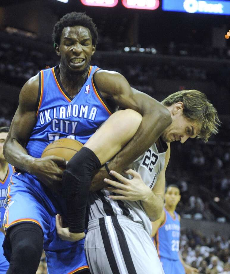 Tiago Splitter of the Spurs (right) battles with Hasheem Thabeet of the Thunder at the AT&T Center on Thursday, Nov. 1, 2012. The game was the home opener for the Spurs.