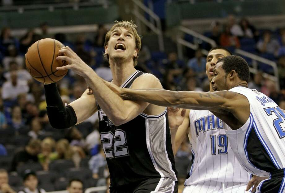 The Spurs' Tiago Splitter (22) looks to shoot against the Magic's Gustavo Ayon (19) and DeQuan Jones (20) during the second half of an NBA preseason basketball game, Sunday,Oct. 21, 2012, in Orlando, Fla. Orlando won 104-100.