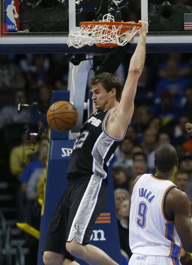 Spurs center Tiago Splitter (22) dunks in front of Thunder forward Serge Ibaka (9) during in Oklahoma City, Monday, Dec. 17, 2012. Oklahoma City won 107-93.