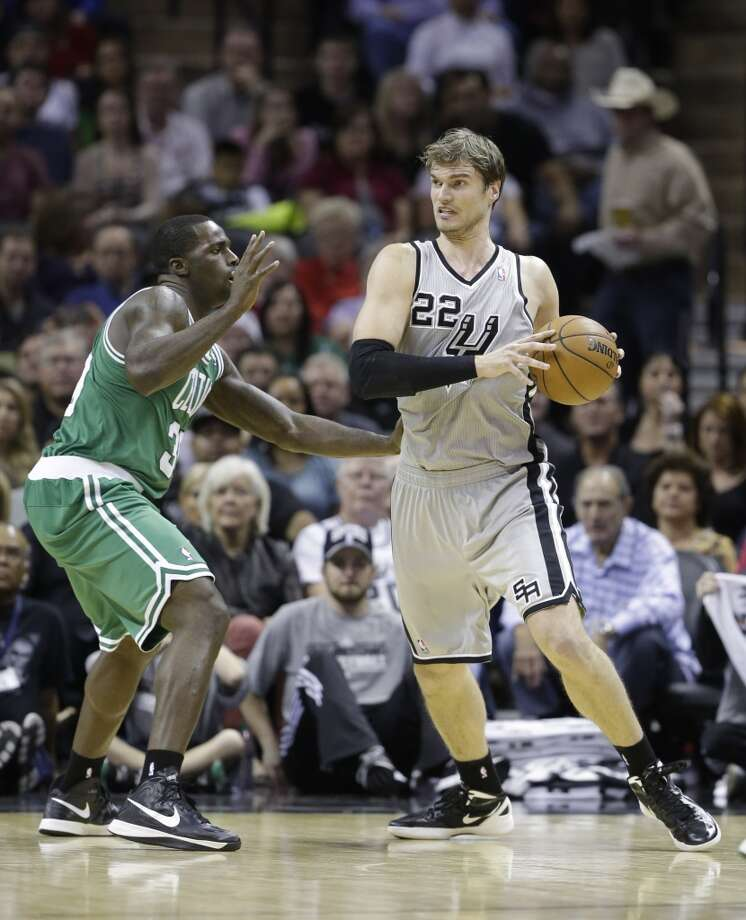 The Spurs' Tiago Splitter (22) drives around the Celtics' Brandon Bass during the first quarter, Saturday, Dec. 15, 2012, in San Antonio.