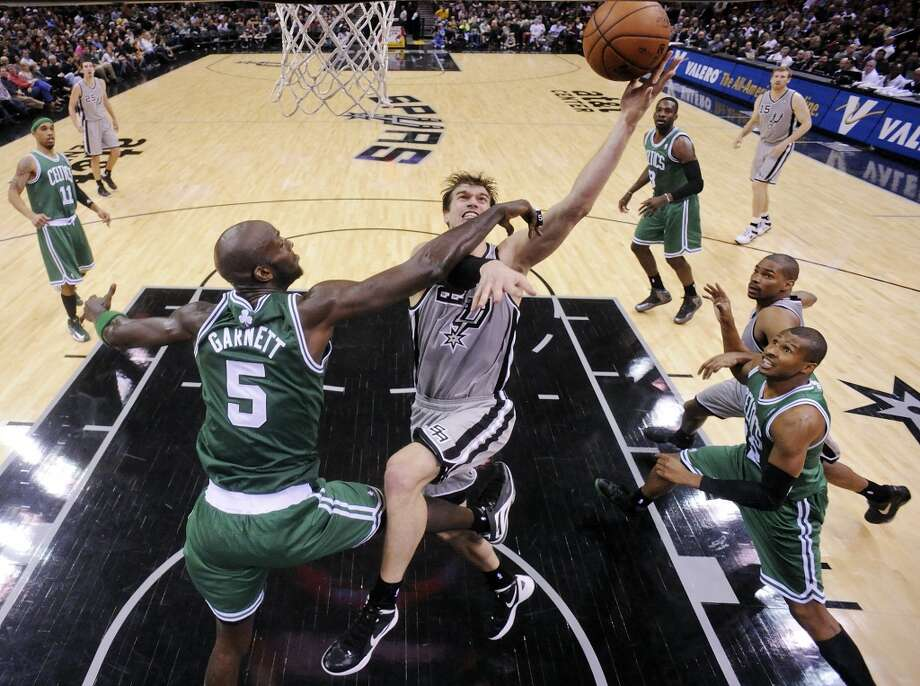 The Spurs' Tiago Splitter shoots against the Celtics' Kevin Garnett during second half action Saturday Dec. 15, 2012 at the AT&T Center. The Spurs won 103-88.