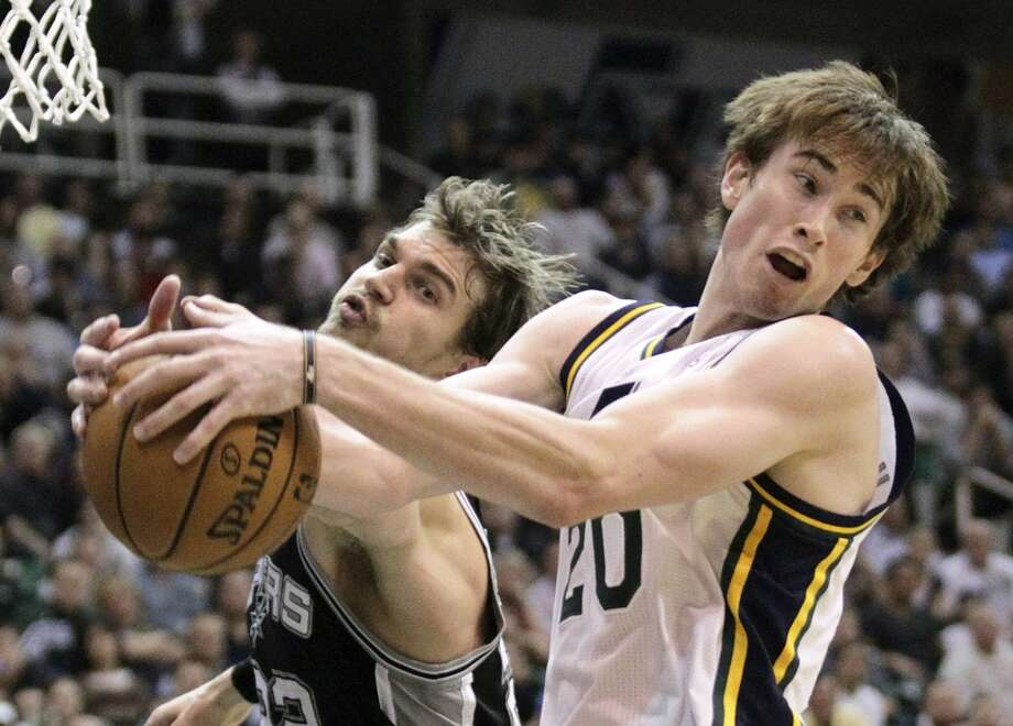 Jazz guard Gordon Hayward (right) and Spurs forward Tiago Splitter battle for a loose ball in the second half Wednesday, Dec.12, 2012, in Salt Lake City.