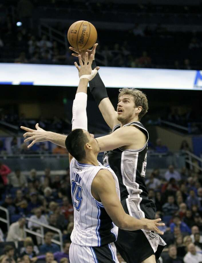 The Spurs' Tiago Splitter (right)  takes a shot over the Magic's Gustavo Ayon (19) during the second half on  Wednesday, Nov.  28, 2012, in Orlando, Fla. The Spurs won 110-89.