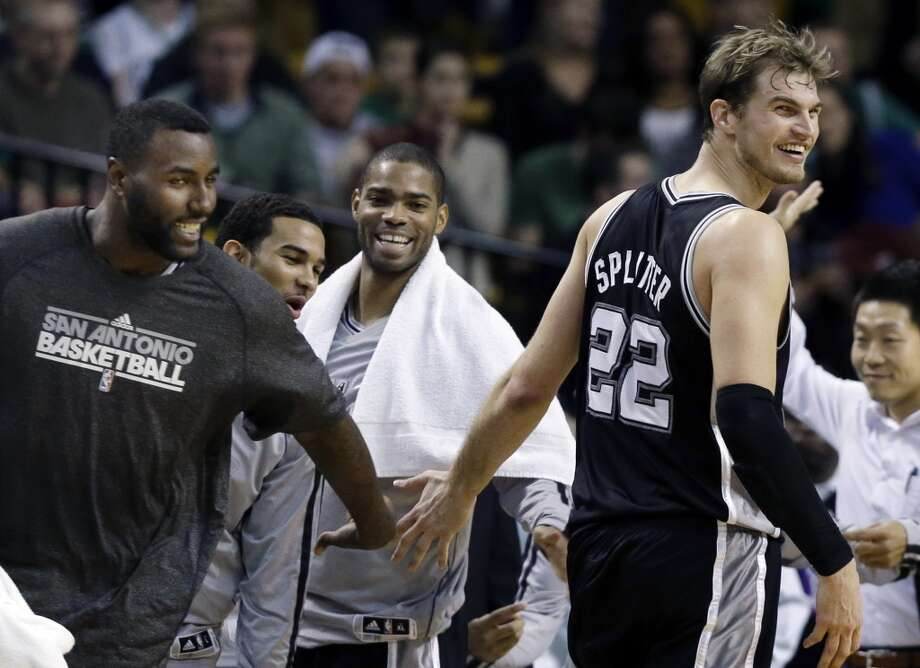 Spurs forward Tiago Splitter (22) receives congratulation from center DeJuan Blair (far left) and others on the bench late in the fourth quarter against the Celtics in Boston, Wednesday, Nov. 21, 2012. The Spurs won 112-100.