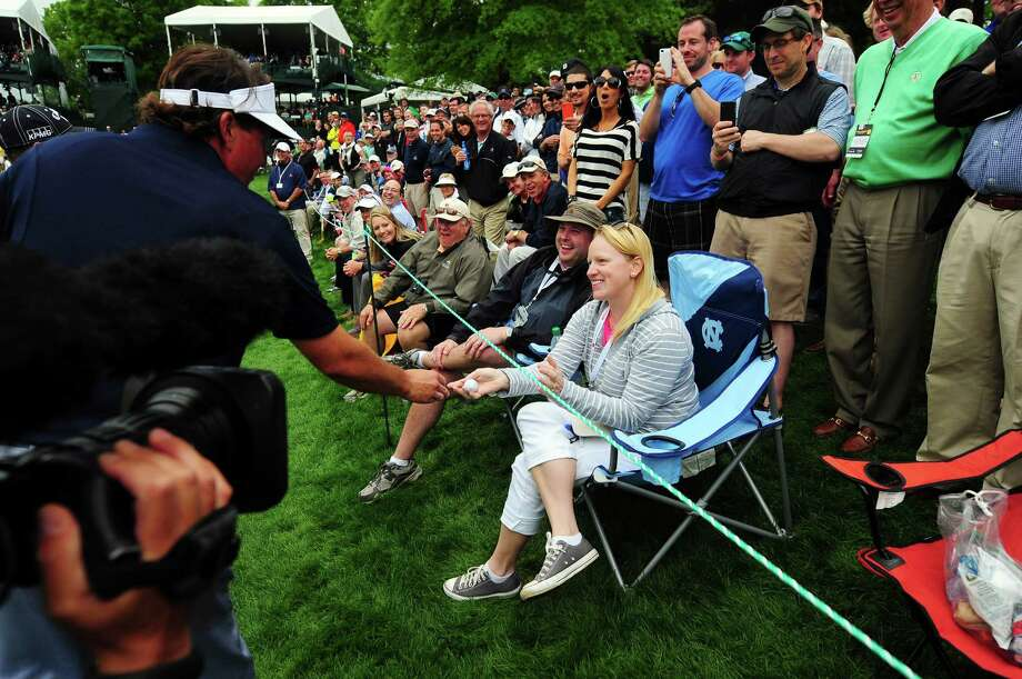 Phil Mickelson gives a ball to Marsha Thrasher of Charlotte, N.C., after his ball hit her chair near the 15th green at the Wells Fargo Championship. Photo: Jeff Siner, MBR / Charlotte Observer
