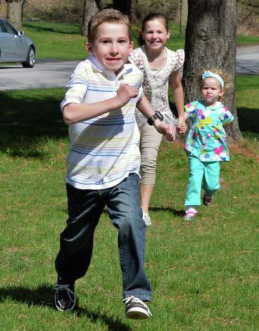 Six-year-old Callahan Urkuhart, left, races his sisters Olivia, 8 and Breigh, 3, at right, across the front lawn of their Troy home Tuesday April 30, 2013.  Callahan will be recognized as this year's Heart Hero at the Heart Walk. He had a congenital heart defect and underwent surgery at 9 days old. He's healthy, active and athletic now.  (John Carl D'Annibale / Times Union) Photo: John Carl D'Annibale / 10022147A
