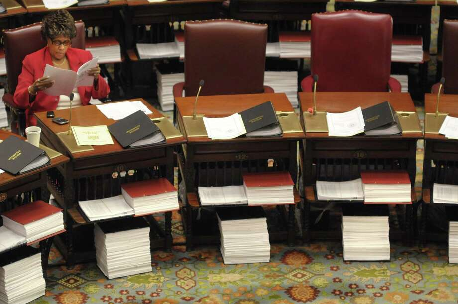 Senator Shirley Huntley, reads through some paperwork at her desk on the floor of the New York State Senate before the start of a Senate session on Tuesday, March 29, 2011.  The stacks of paper beneath the Senator' desks contain budget bills that will be voted on.  (Paul Buckowski / Times Union) Photo: Paul Buckowski
