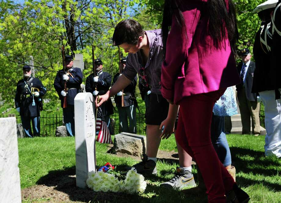 Connor Roberts, a sixth grader at Lincoln Elementary School in Schenectady, places a flag at the grave of Civil War veteran Pvt. Thomas Ray, 21, of Albany, during a special dedication ceremony Friday morning, May 3, 2013, at St. Agnes Cemetery in Menands, N.Y.  Students adopted the soldier from the 177th N.Y. volunteers infantry regiment 150 years after he died in Louisiana.  (Will Waldron/Times Union) Photo: Will Waldron