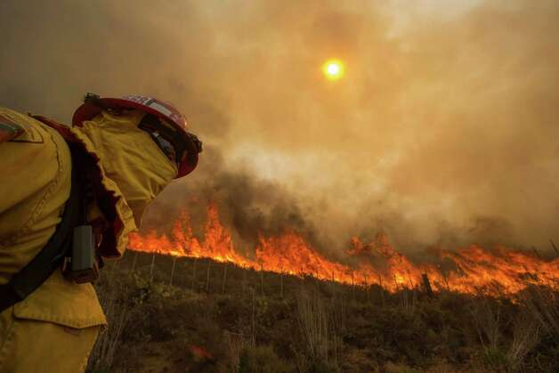 A firefighter keeps watch as the wildfire burns along a hillside in Point Mugu , Calif. Friday, May 3, 2013. Firefighters got a break as gusty winds turned into breezes, but temperatures remained high and humidity levels are expected to soar as cool air moved in from the ocean and the Santa Ana winds retreated. (AP Photo/Ringo H.W. Chiu) Photo: Ringo H.W. Chiu, Associated Press / FR170512 AP
