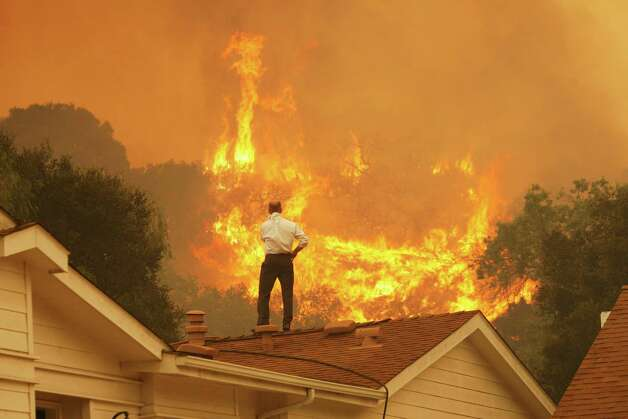 A man on a rooftop looks at approaching flames as the Springs fire continues to grow on May 3, 2013 near Camarillo, California. The wildfire has spread to more than 18,000 acres on day two and is 20 percent contained. Photo: David McNew, Getty Images / 2013 Getty Images