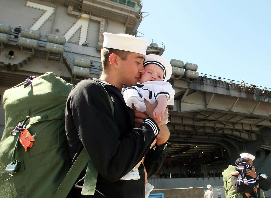 Jacob James nuzzles his 5-month-old daughter Annabelle after arriving on the USS John C. Stennis at Naval Base Kitsap-Bremerton  on Friday, May, 3, 2013 in Bremerton, Wash. The ship with 3,000 sailors completed an eight-month deployment Friday afternoon that covered 66,000 miles through the western Pacific. The Navy says aircraft from its deck flew more than 1,300 missions in direct support of fighting in Afghanistan. (AP Photo/Kitsap Sun, Meegan M. Reid) Photo: MEEGAN M. REID, Associated Press / KITSAP SUN