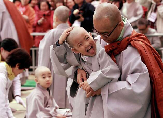 A boy feels his head after it was shaven during a ceremony before Buddha's upcoming birthday on May 17 at the Jogye temple in Seoul, South Korea, Friday, May 3, 2013. Ten children entered the temple to experience life with monks for 16 days leading up to Buddha's birthday. (AP Photo/Ahn Young-joon) Photo: Ahn Young-joon, Associated Press / AP