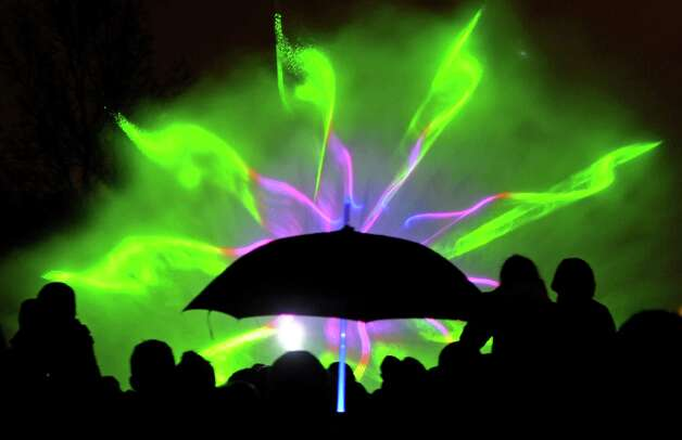 People watch a fountain light show in Warsaw, Poland, Friday, May 3, 2013. Thousands of spectators came to a Old Town park to see the first show in this year's season. (AP Photo/Alik Keplicz) Photo: Alik Keplicz, Associated Press / AP