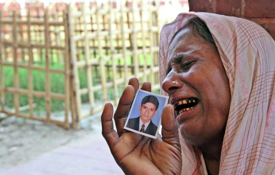 A Bangladeshi woman, holding a photo of her missing son, cries at a graveyard after a garments factory building collapse in Savar near Dhaka, Bangladesh, Friday May 3, 2013. Authorities suspended the mayor of the suburb of Savar, where the building was located, and arrested an engineer who called for the building's evacuation last week but was also accused of helping the owner add three illegal floors to the eight-story structure. (AP Photo/Palash Khan) Photo: Palash Khan, Associated Press / AP