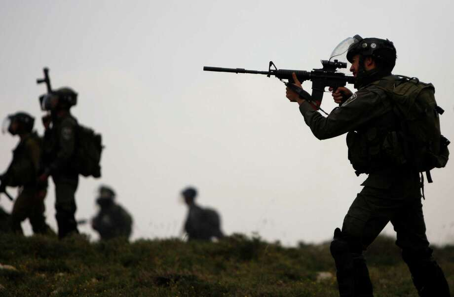 Israeli border police officers fire rubber bullets towards Palestinians during clashes between Palestinians and Jewish settlers near the West Bank village of Deir Jarir near Ramallah, Friday, May 3, 2013. Tensions are high in the West Bank, captured by Israel in the 1967 Mideast war and claimed by Palestinians as part of their future state. (AP Photo/Majdi Mohammed) Photo: Majdi Mohammed, Associated Press / AP