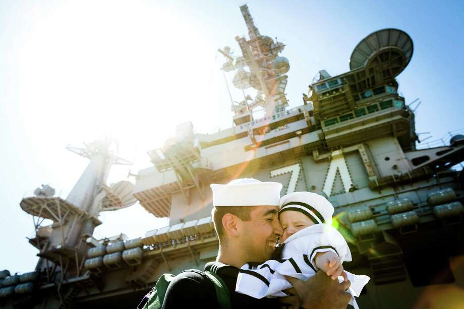 Jacob James, center, hugs his five-month-old daughter Annabelle James, right, after stepping off of the USS John C. Stennis aircraft carrier following an eight-month deployment Friday, May 3, 2013, in Bremerton. The crew was stationed in the 5th and 7th fleet areas of U.S. responsibility, namely the Persian Gulf. Photo: JORDAN STEAD, SEATTLEPI.COM / SEATTLEPI.COM
