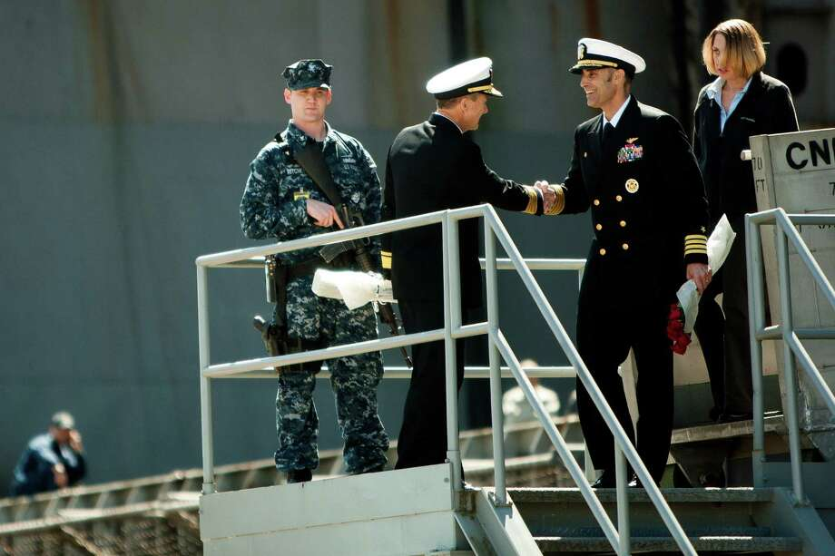 Shaking hands, Commander Troy Shoemaker, left, and Captain Ronald Reis, right, exit the USS John C. Stennis aircraft carrier following an eight- month deployment Friday, May 3, 2013, in Bremerton. The crew was stationed in the 5th and 7th fleet areas of U.S. responsibility, namely the Persian Gulf. Photo: JORDAN STEAD, SEATTLEPI.COM / SEATTLEPI.COM