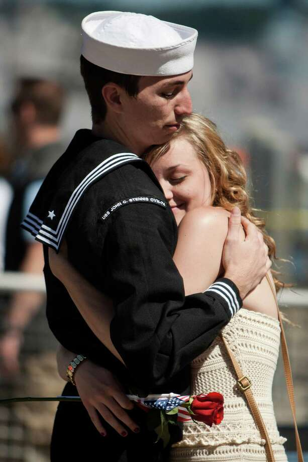 Brandon Rimes, left, hugs his wife Sam Rimes, right, after leaving the USS John C. Stennis aircraft carrier following an eight-month deployment Friday, May 3, 2013, in Bremerton. The crew was stationed in the 5th and 7th fleet areas of U.S. responsibility, namely the Persian Gulf. Photo: JORDAN STEAD, SEATTLEPI.COM / SEATTLEPI.COM