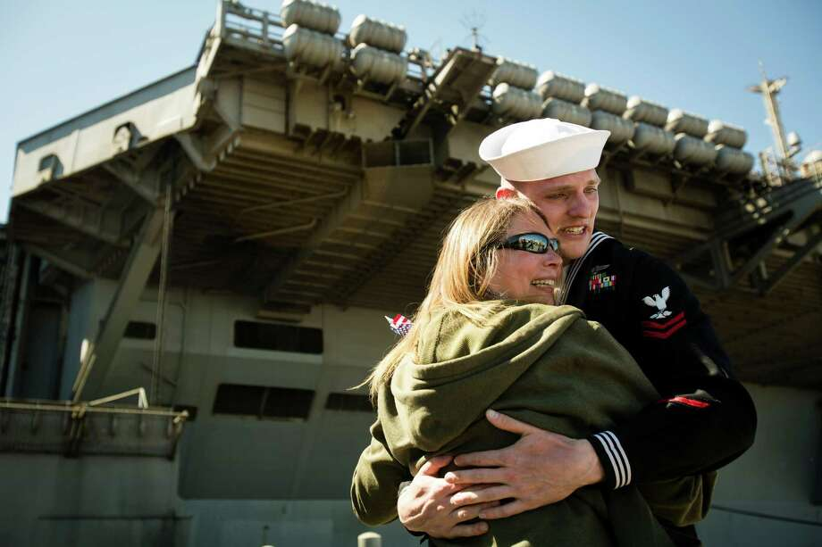 William Godfrey, right, hugs his mother Tammy Decker, center right, following an eight-month deployment Friday, May 3, 2013, in Bremerton. The crew was stationed in the 5th and 7th fleet areas of U.S. responsibility, namely the Persian Gulf. Photo: JORDAN STEAD, SEATTLEPI.COM / SEATTLEPI.COM