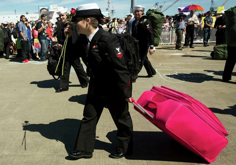 While most sailors towed Navy-issued bags, one tugged her large pink suitcase home following an eight-month deployment Friday, May 3, 2013, in Bremerton. The crew was stationed in the 5th and 7th fleet areas of U.S. responsibility, namely the Persian Gulf. Photo: JORDAN STEAD, SEATTLEPI.COM / SEATTLEPI.COM